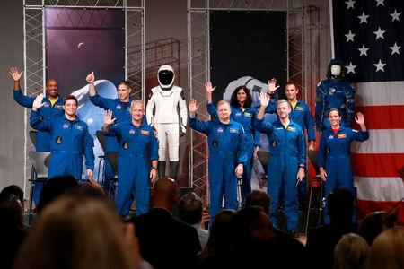 The astronauts assigned to crew the first flight tests and missions of the Boeing CST-100 Starliner and SpaceX Crew Dragon acknowledge the media upon introduction at NASA's Johnson Space Center in Houston