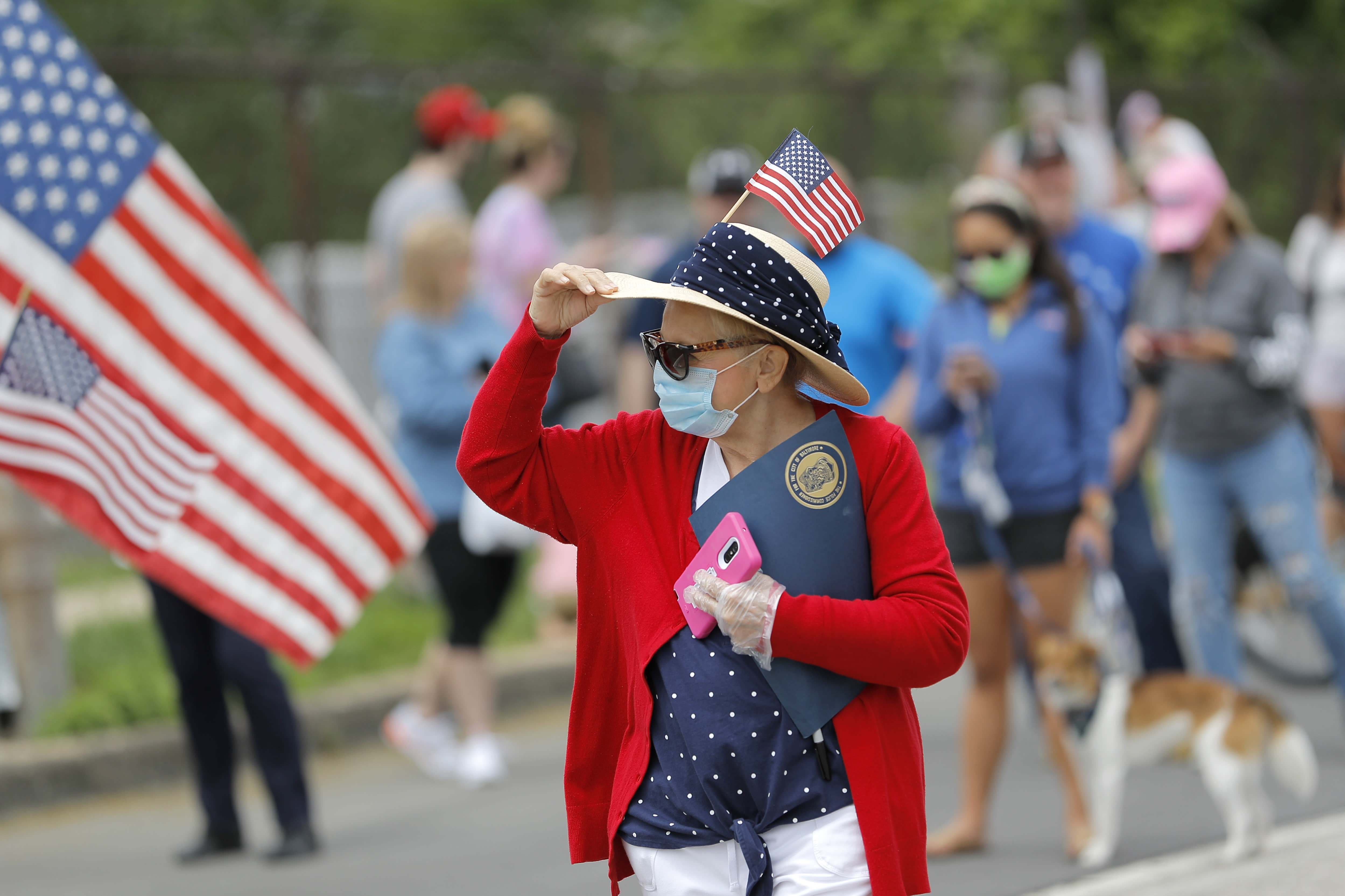A woman holds on to her hat as she gathers with people outside of Fort McHenry National Monument and Historic Shrine, where President Donald Trump attends a Memorial Day ceremony, Monday, May 25, 2020, in Baltimore. (AP Photo/Julio Cortez)