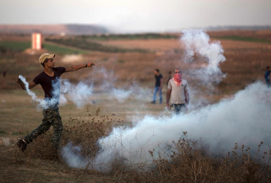 A Palestinian protester throws back a tear gas canister during clashes with Israeli soldiers near the border fence between Israel and the central Gaza Strip east of Bureij on October 15, 2015