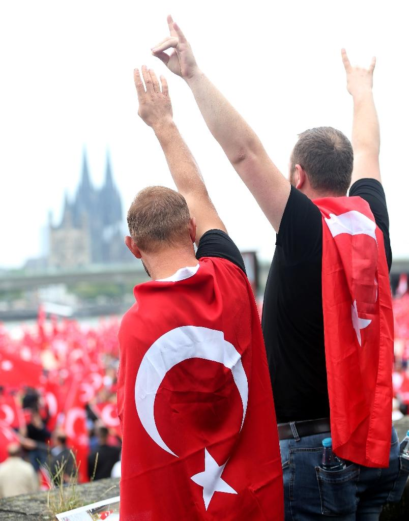 "Waving the Turkish flag and chanting ""Turkey"", the demonstrators turned the rally site next to the River Rhine in Cologne into a sea of red as they began the demonstration by singing the Turkish and German national anthems (AFP Photo/Oliver Berg)"