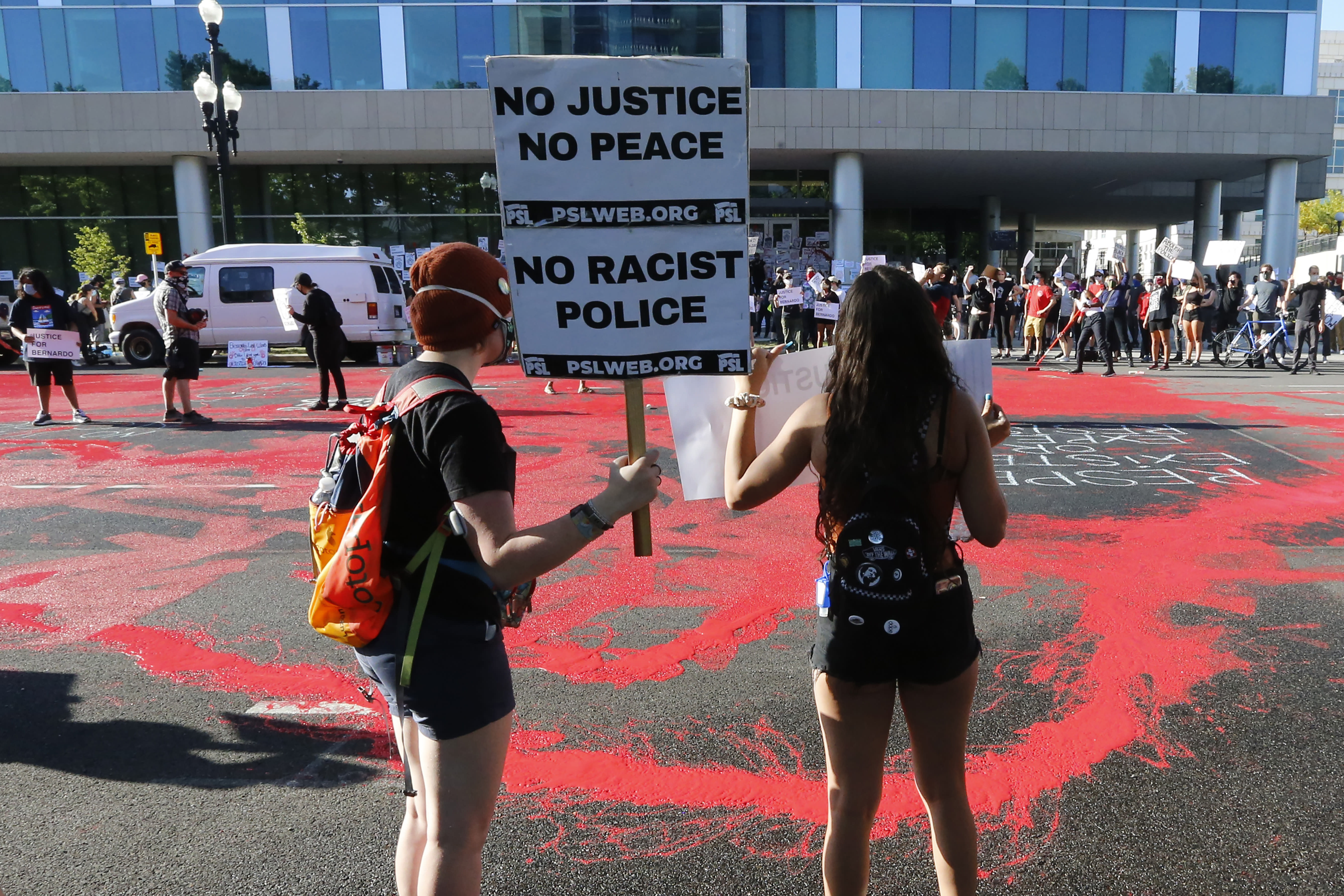 FILE - In this July 9, 2020, file photo, protesters gather in front of district attorney's office in Salt Lake City. Some Black Lives Matter protesters in Utah could face up to life in prison if they're convicted of splashing red paint and smashing windows during a protest, a potential punishment that stands out among demonstrators arrested around the country and one that critics say doesn't fit the alleged crime. (AP Photo/Rick Bowmer, File)