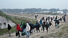 The Latest: Buses start moving migrants out of French camp