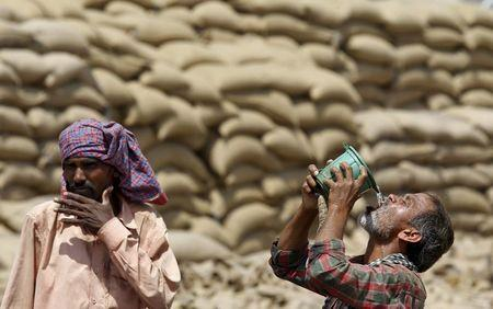 A labourer drinks water as another looks on, on a hot summer day at a grain market in Chandigarh