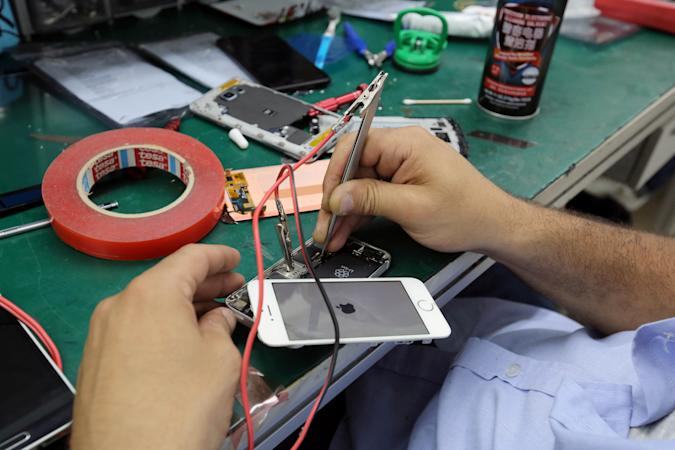 A technician repairs an iPhone at the Class cellphone store in Beirut, Lebanon July 6, 2017. REUTERS/Aziz Taher