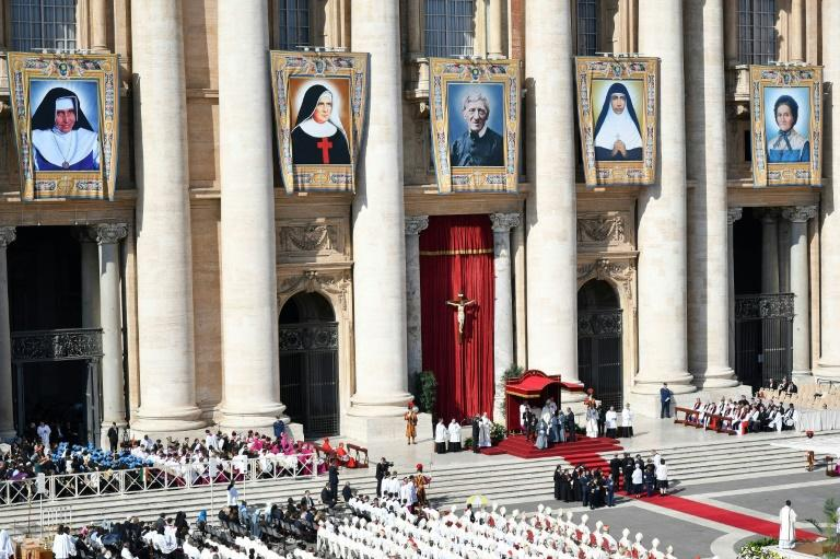 Giant portraits of the new saints were hung from Saint Peter's Basilica for the ceremony which attracted tens of thousands of pilgrims (AFP Photo/Alberto PIZZOLI)