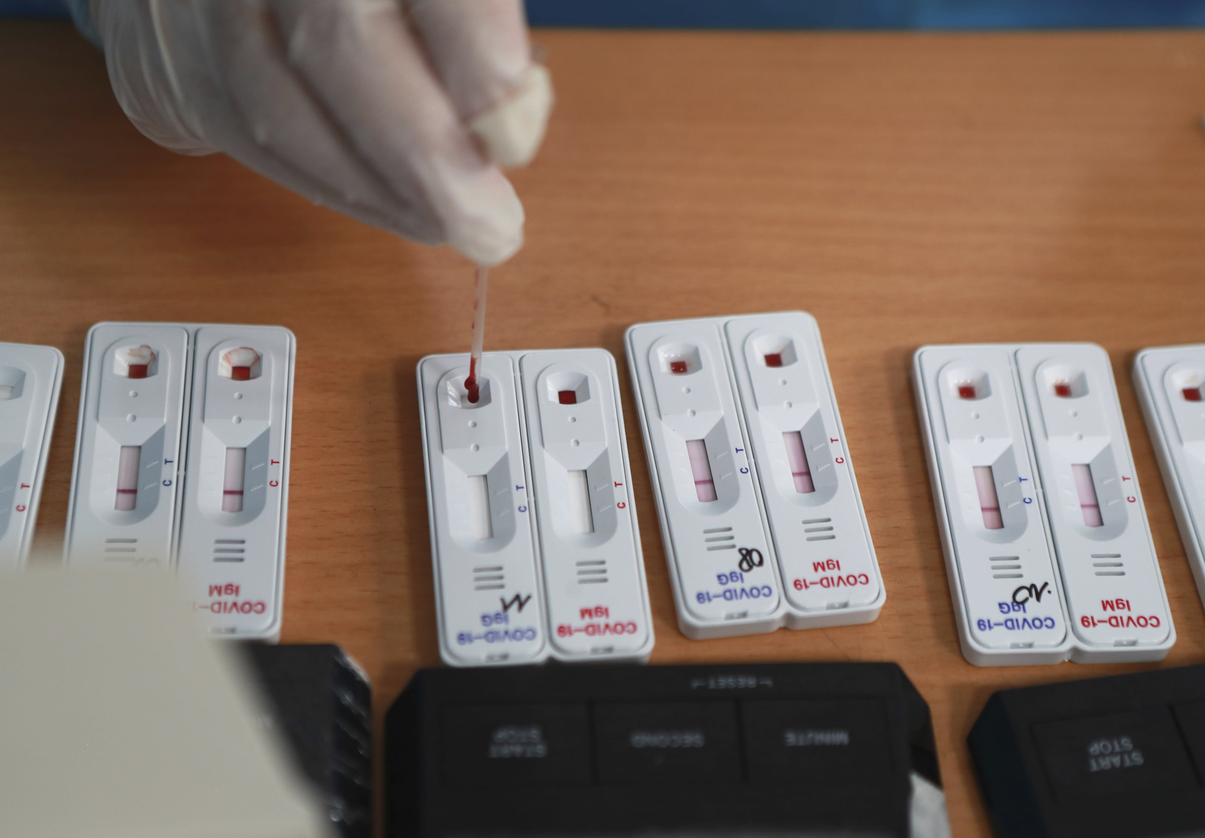 A health worker drops drawn blood on a test kit of COVID-19 in Hanoi, Vietnam, Friday, July 31, 2020. Vietnam reported on Friday the country's first death of a person with the coronavirus as it struggles with a renewed outbreak after 99 days without any cases. (AP Photo/Hau Dinh)