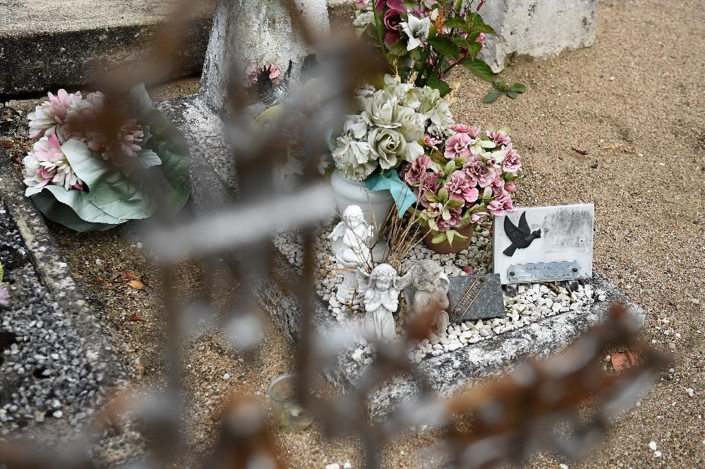 "To this day people regularly replace the flowers on her grave, where the unnamed tombstone reads: ""Here rests an angel"" (AFP Photo/GUILLAUME SOUVANT)"