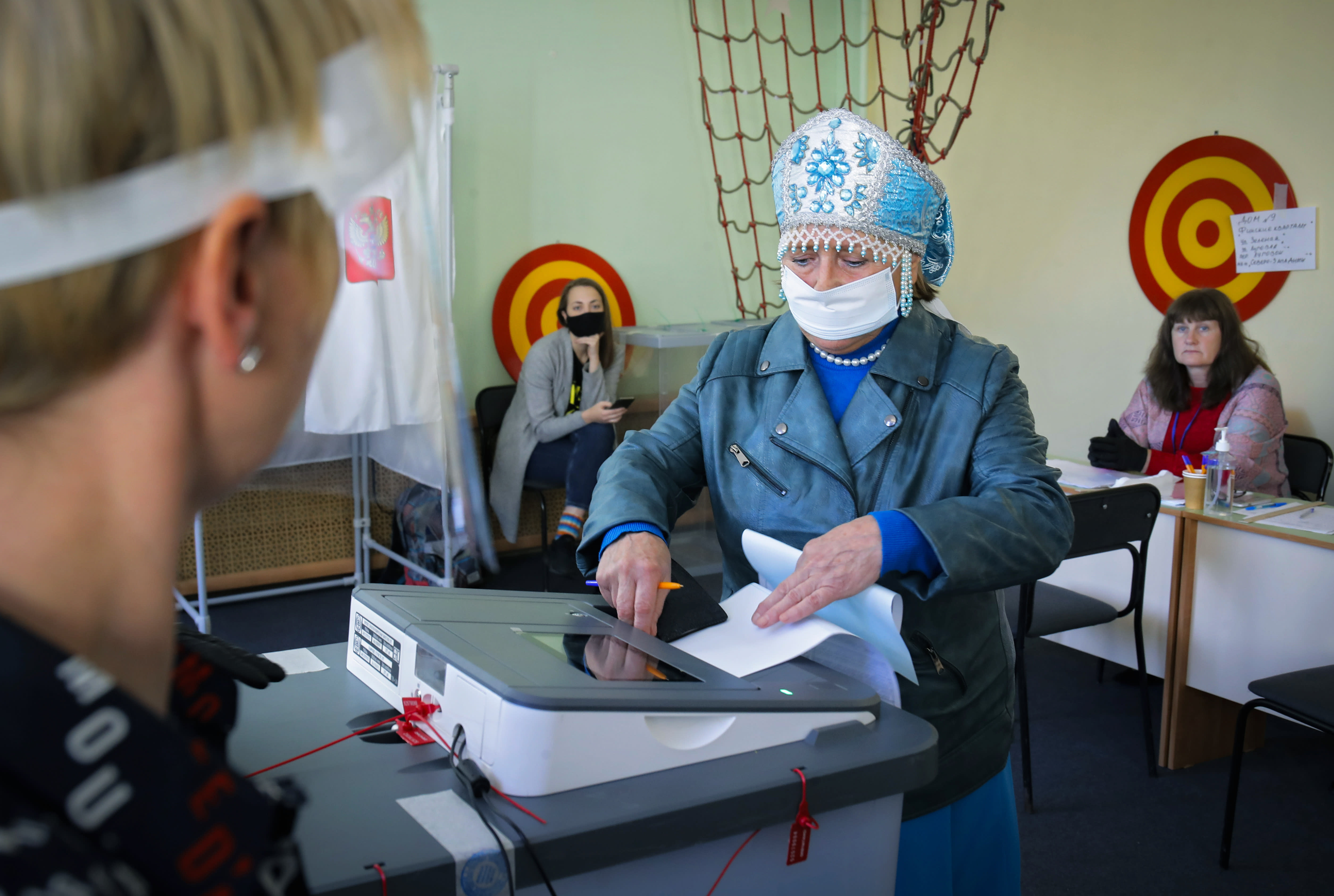 A woman wearing a face mask to protect against coronavirus infection casts her ballot at a poling station during Leningrad region's governor and municipal elections in Luppolovo village, outside St.Petersburg, Russia, Sunday, Sept. 13, 2020. Leningrad region is the territory surrounding St. Petersburg. The elections are held to choose governors and legislators in about half of Russia's regions. (AP Photo/Dmitri Lovetsky)