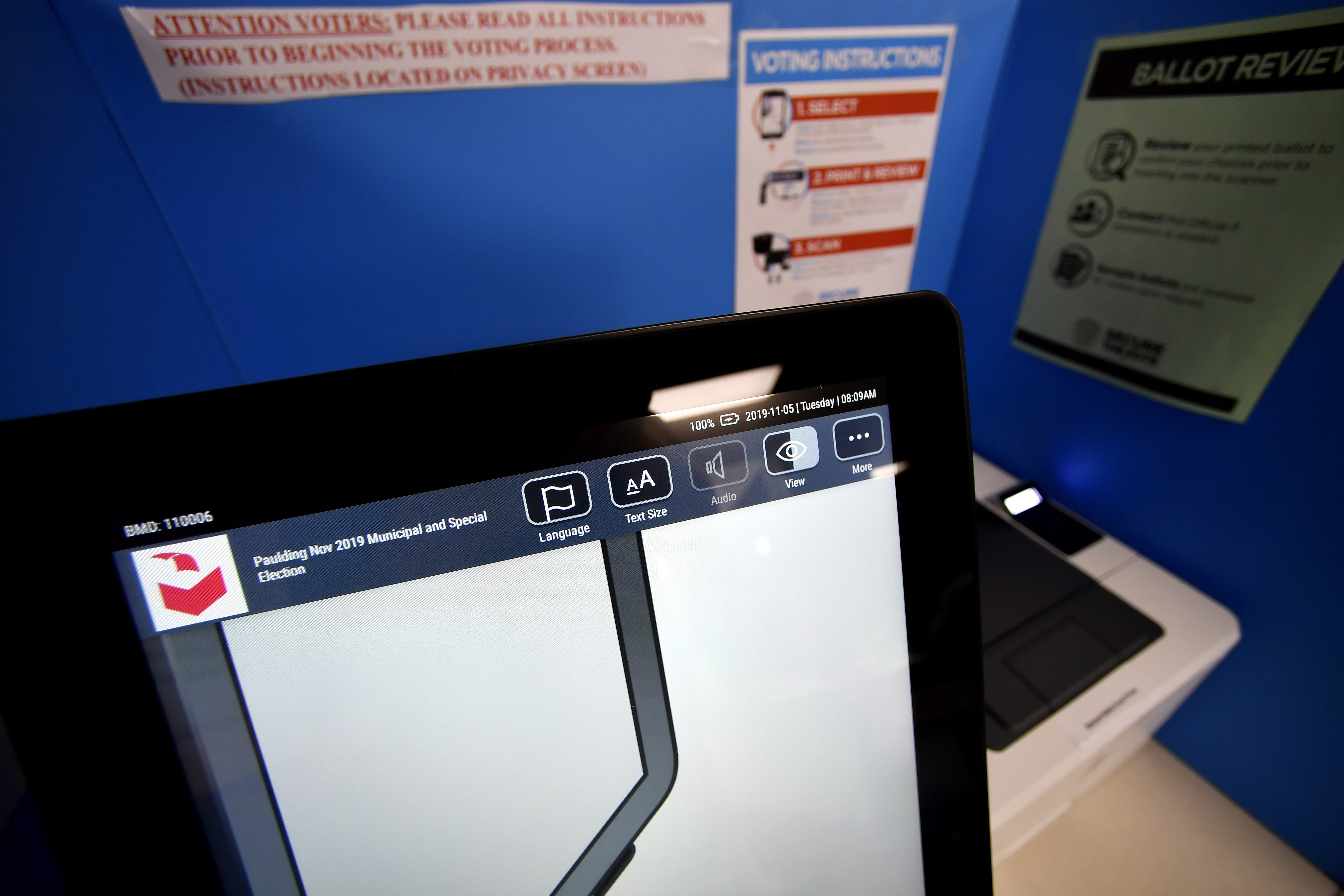 FILE-In this Tuesday, Nov. 5, 2019 file photo, a touchscreen voting machine and printer are seen in a voting booth, in Paulding, Ga. Voting integrity advocates will try this week to convince a federal judge that the state of Georgia should scrap its touchscreen voting machines in favor of hand-marked paper ballots, while the state will ask her not to order any changes, especially so close to an election. (AP Photo/Mike Stewart, File)