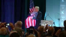 Trump embraces flag, literally