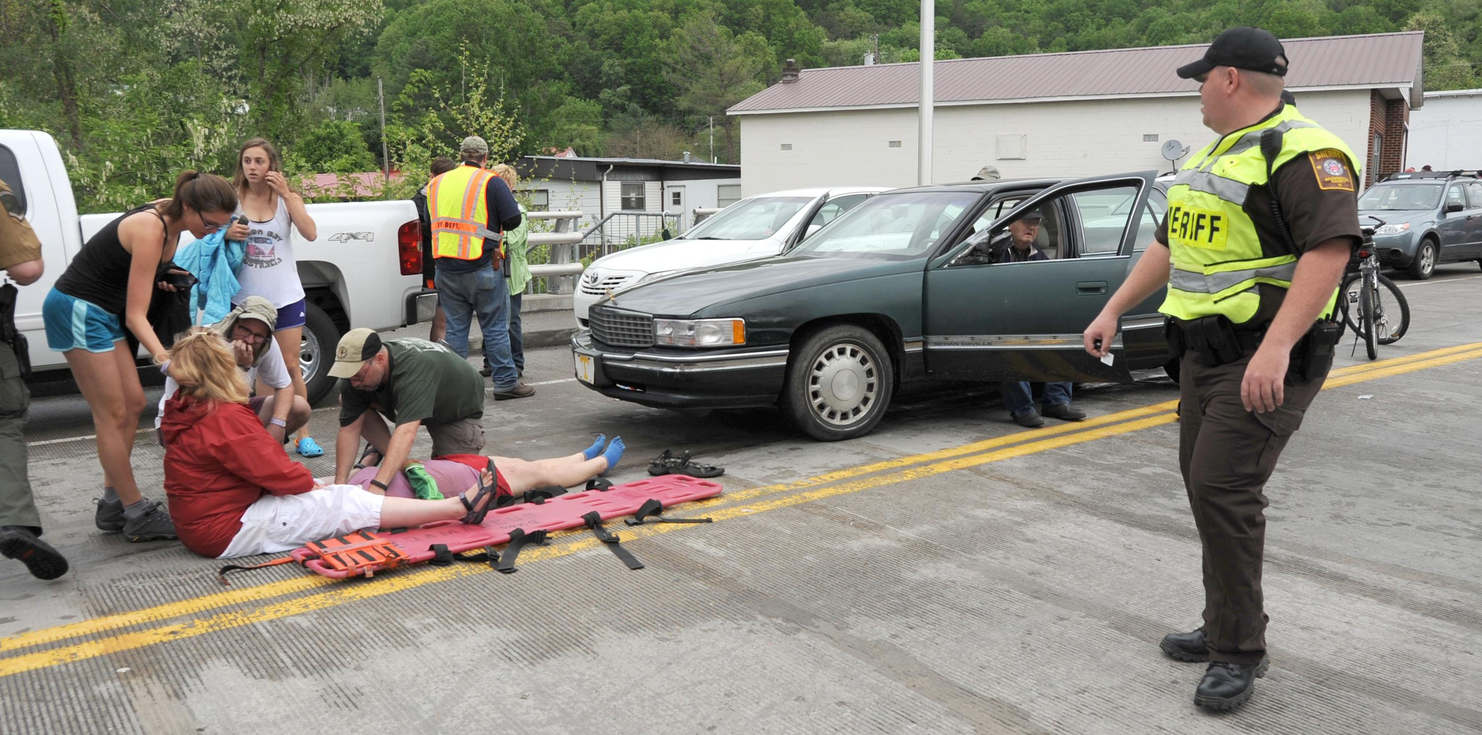 Emergency personnel respond to one of the people hit by a car, at right, during the beginning of the Hikers Parade at the Trail Days festival in Damascus, Va., Saturday, May 18, 2013. Witnesses said the car drove into a crowd at the parade and hurt several people, but the nature of their injuries wasn't immediately known. (AP Photo/Bristol Herald Courier, Earl Neikirk)