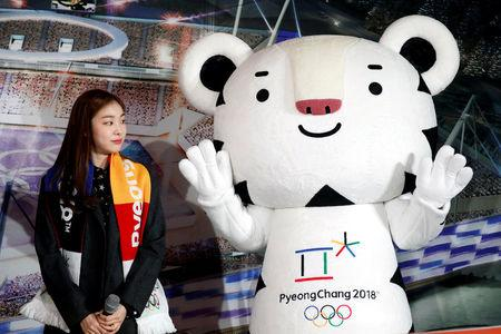 """FILE PHOTO: Kim Yuna looks at the Olympic mascot """"Soohorang"""" during the ceremony to mark a year to the 2018 PyeongChang Winter Olympic Games in Gangneung"""
