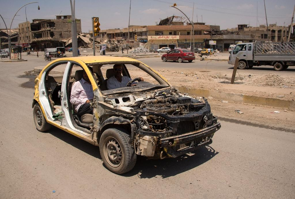 Iraqis drive a stripped-down car in west Mosul on July 12, 2017, days after the government announced victory over jihadists in the city (AFP Photo/FADEL SENNA)