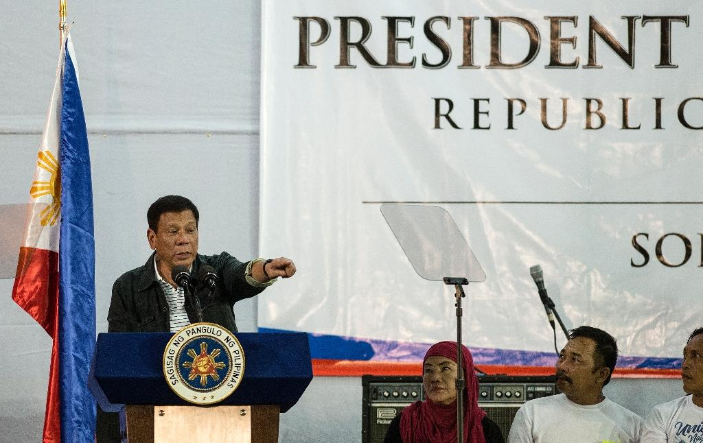 Philippine President Rodrigo Duterte gestures to the crowd he visited composed of families living in slum area of Manila on June 30, 2016 (AFP Photo/Noel Celis)