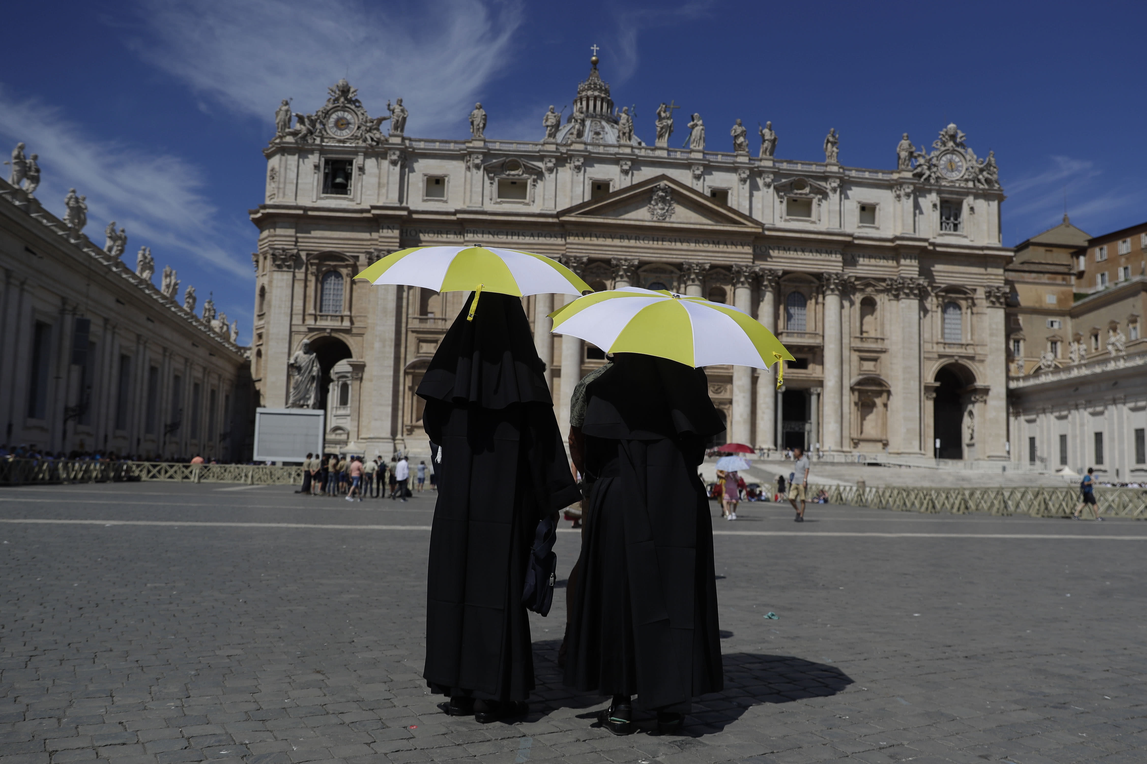 Nuns shelters from the sun with their umbrellas bearing the colors of the Vatican flag prior to the start of Pope Francis Angelus prayer in St. Peter's Square at the Vatican, Sunday, Aug. 4, 2019. Pope Francis told a crowd gathered in St. Peter's Square for the weekly Angelus blessing Sunday that ''I am spiritually close to the victims of the episodes of violence that have bloodied Texas, California and Ohio, in the United States, striking defenseless people.'' (AP Photo/Gregorio Borgia)