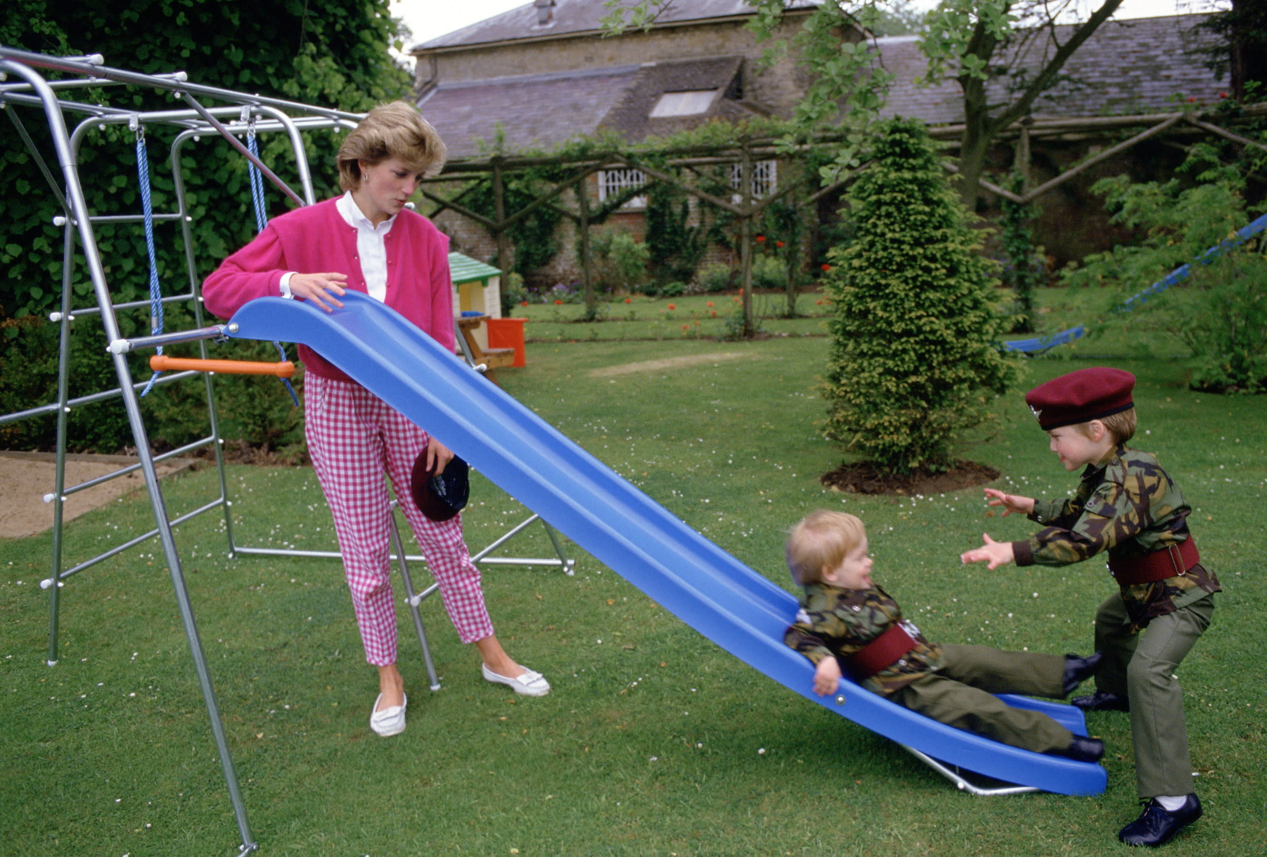 TETBURY, UNITED KINGDOM - JULY 18:  Princess Diana With Her Sons Prince William And Prince Harry Playing On A Slide In The Gardens Of Highgove House. The Boys Are Wearing The Uniforms Of The 1st Battalion Of The Parachute Regiment Of Which Their Father Is The Colonel-in-chief. Princess Diana Is Wearing A Gingham Style Pair Of Trousers.  (Photo by Tim Graham/Getty Images)