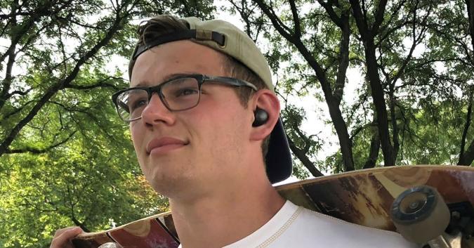 A man modeling the Brio SkyBorn S4 true wireless earbuds.