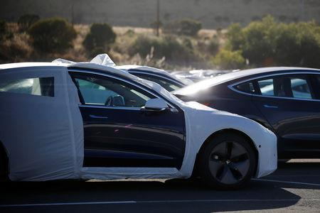 A partially wrapped Tesla Model 3 electric vehicle is seen at a lot in Richmond, California, U.S. June 22, 2018. Picture taken June 22, 2018. REUTERS/Stephen Lam
