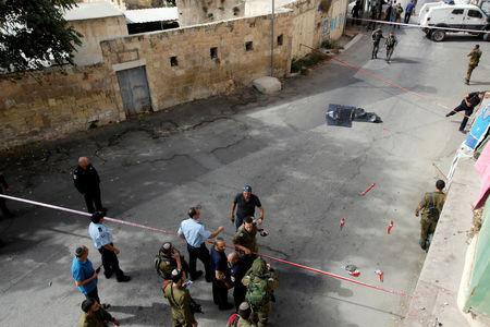 The dead body of a Palestinian is covered as Israeli forces gather at the scene of a stabbing attack in Hebron, in the occupied West Bank October 22, 2018. REUTERS/Mussa Qawasma