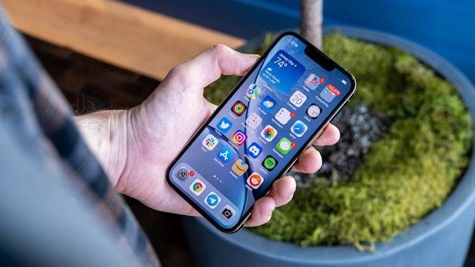 The iPhone 13 Pro, held face up in a person's hand, with the iOS 15 home screen in view.