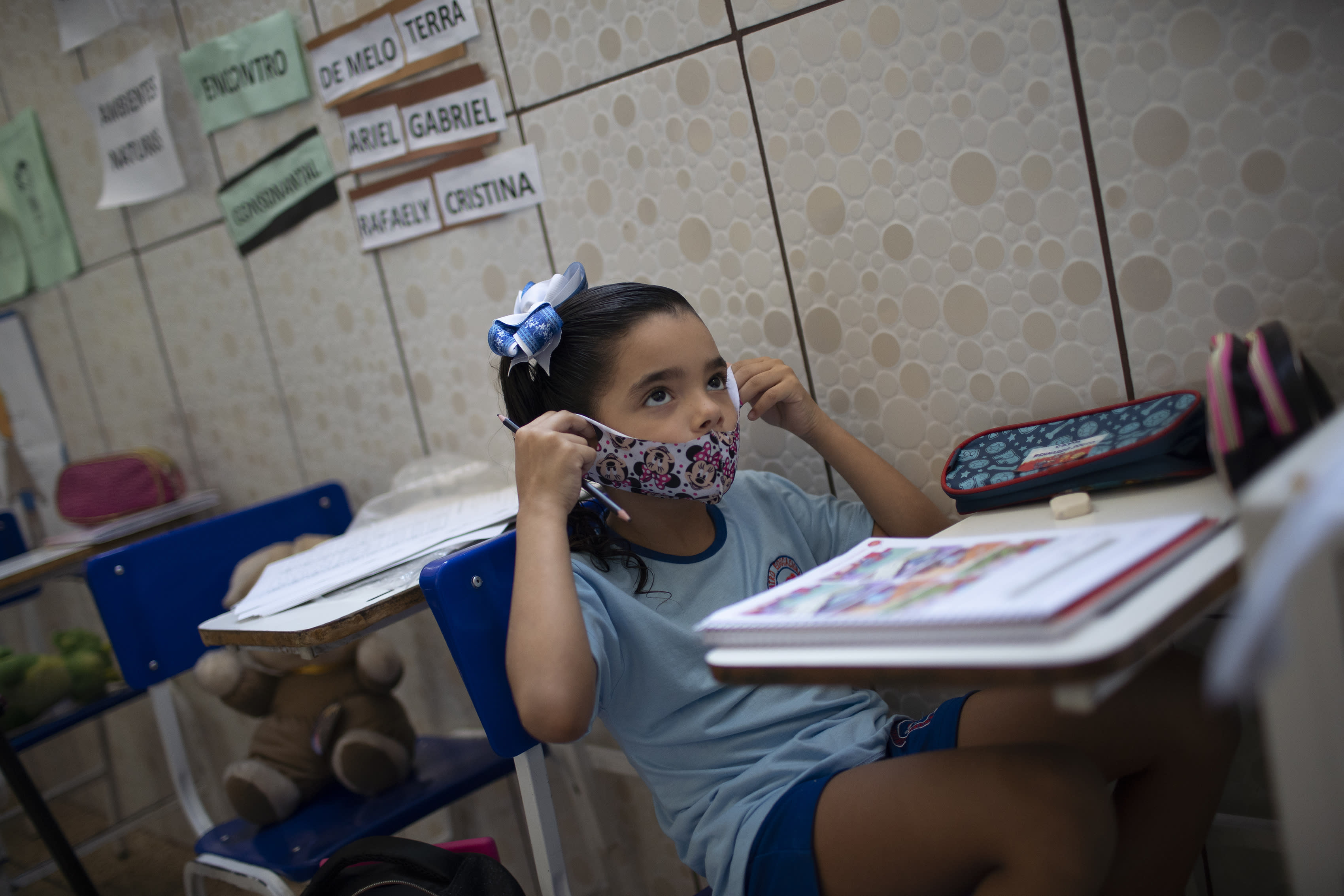 Rafaely de Melo puts on her protective mask during a class at the Pereira Agustinho daycare, nursery school and pre-school, after it reopened amid the new coronavirus pandemic in Duque de Caxias, Monday, July 6, 2020. The city of Manaus in the Amazon rainforest and Duque de Caxias in Rio de Janeiro's metropolitan region, became on Monday the first Brazilian cities to resume in-person classes at private schools since the onset of the COVID-19 pandemic, according to the nation's private school federation. (AP Photo/Silvia Izquierdo)
