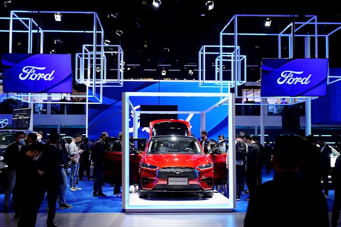 Visitors check a Ford Mustang Mach-E electric vehicle (EV) displayed at the Ford booth during a media day for the Auto Shanghai show in Shanghai, China April 19, 2021. REUTERS/Aly Song