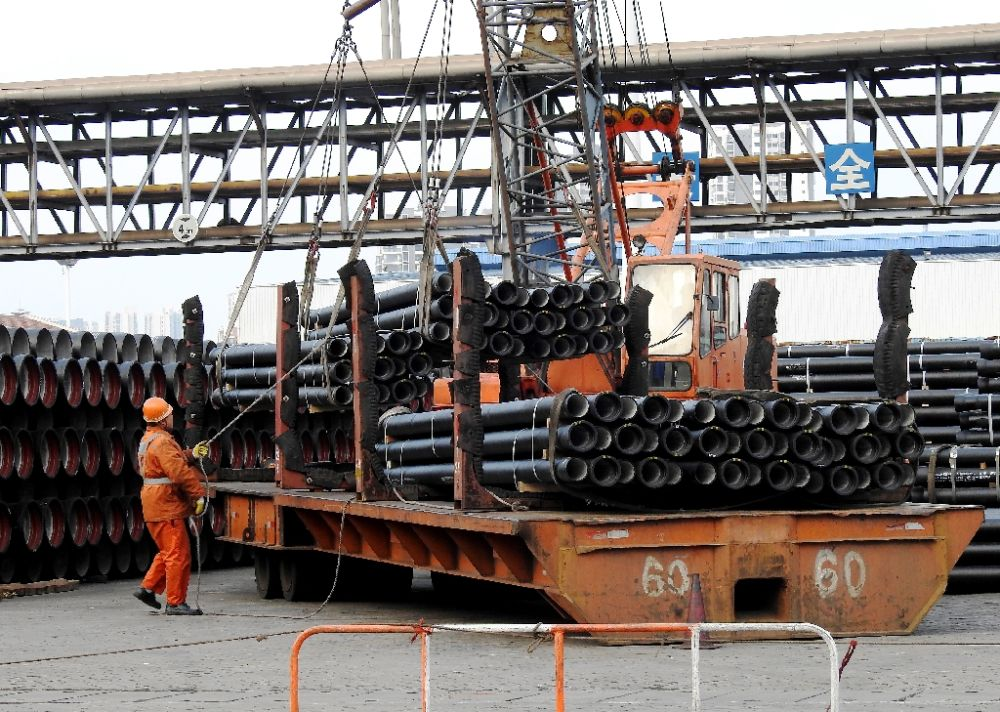 A worker loads steel tubes onto a truck at a logistics center in Lianyungang, east China's Jiangsu province