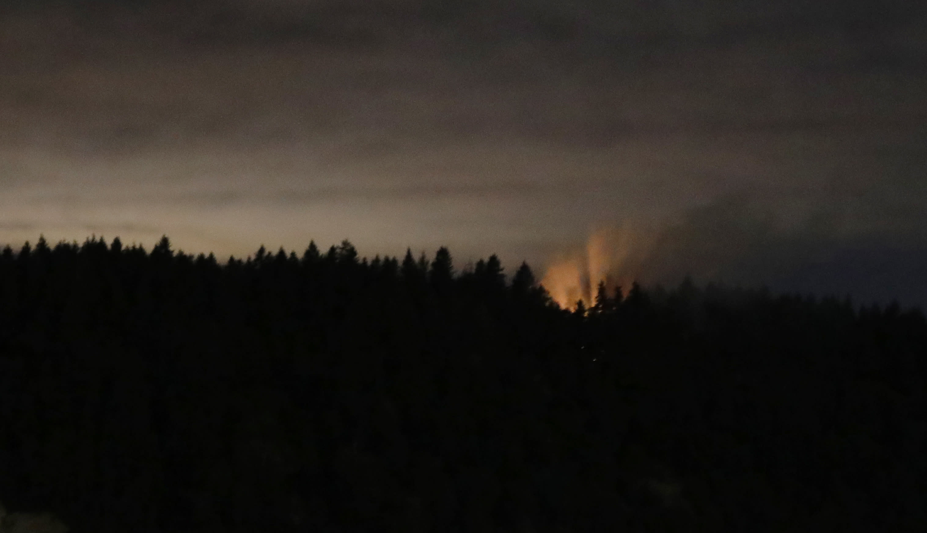 In this long-exposure photo, smoke and an orange glow are seen on Ketron Island in Washington state, early Saturday, Aug. 11, 2018 as viewed from near Steilacoom, Wash. On Friday, an airline mechanic stole an empty Horizon Air turboprop plane, took off from Seattle-Tacoma International Airport and was chased by military jets before crashing onto Ketron, a small island in the Puget Sound, on Friday night, officials said. (AP Photo/Ted S. Warren)
