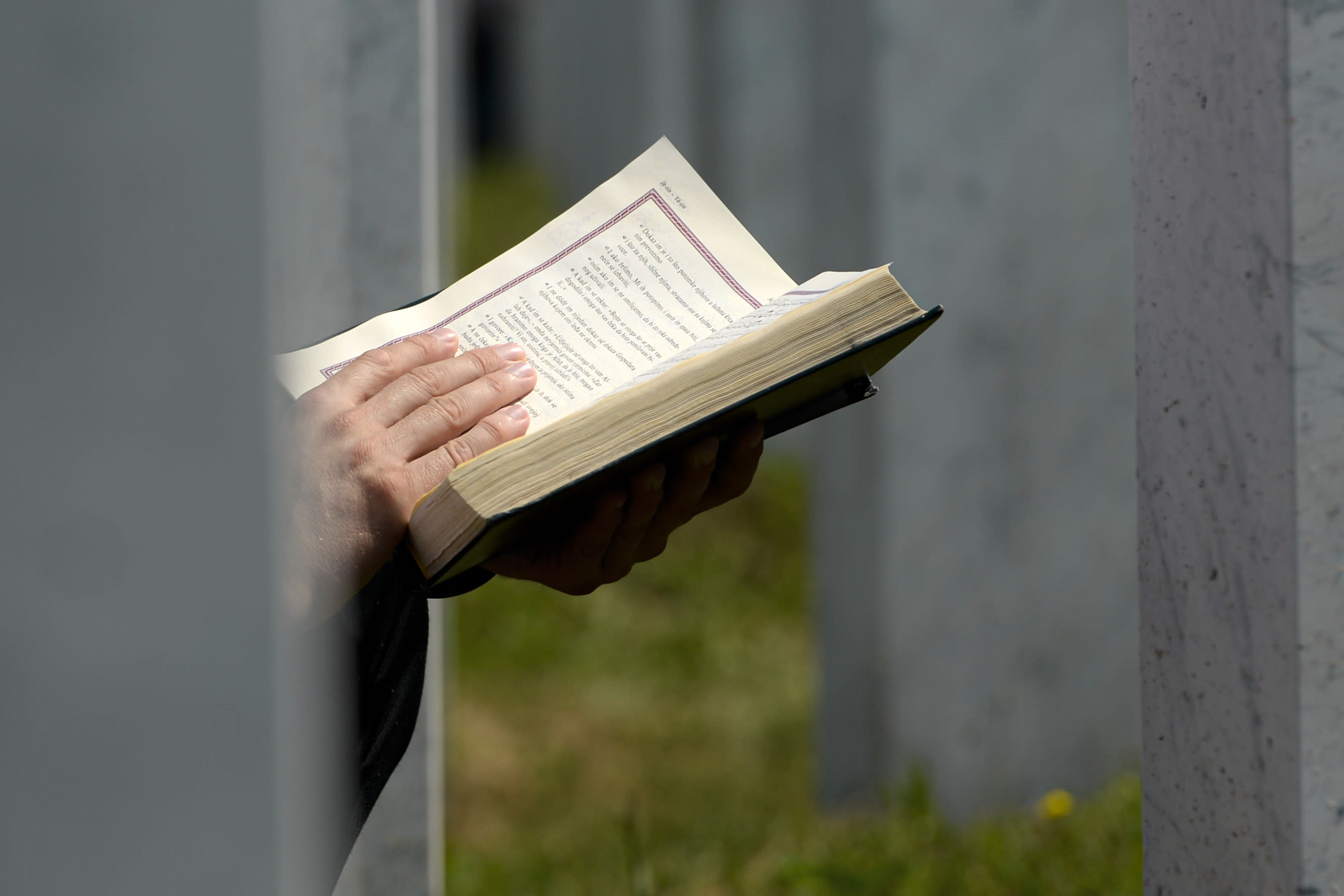 A man prays sitting between grave stones in Potocari, near Srebrenica, Bosnia, Saturday, July 11, 2020. Mourners converged on the eastern Bosnian town of Srebrenica for the 25th anniversary of the country's worst carnage during the 1992-95 war and the only crime in Europe since World War II that has been declared a genocide. (AP Photo/Kemal Softic)