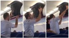 Passenger films man hilariously struggling to get his bag into the overhead bin