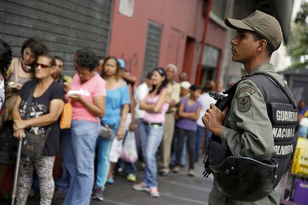 A Venezuelan soldier stands guard next to people forming a line to try to buy cornmeal flour and margarine at a pharmacy in Caracas March 15, 2016. REUTERS/Carlos Garcia Rawlins/File Photo