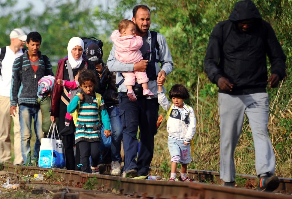 Migrant families walk along a railway track near the border village Roszke, at the Hungarian-Serbian border on August 25, 2015 (AFP Photo/Attila Kisbenedek)