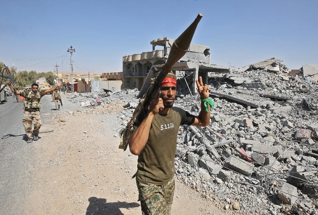 An Iraqi fighter flashes the victory sign while carrying a rocket-propelled grenade launcher in Tal Afar on August 26, 2017 (AFP Photo/AHMAD AL-RUBAYE)