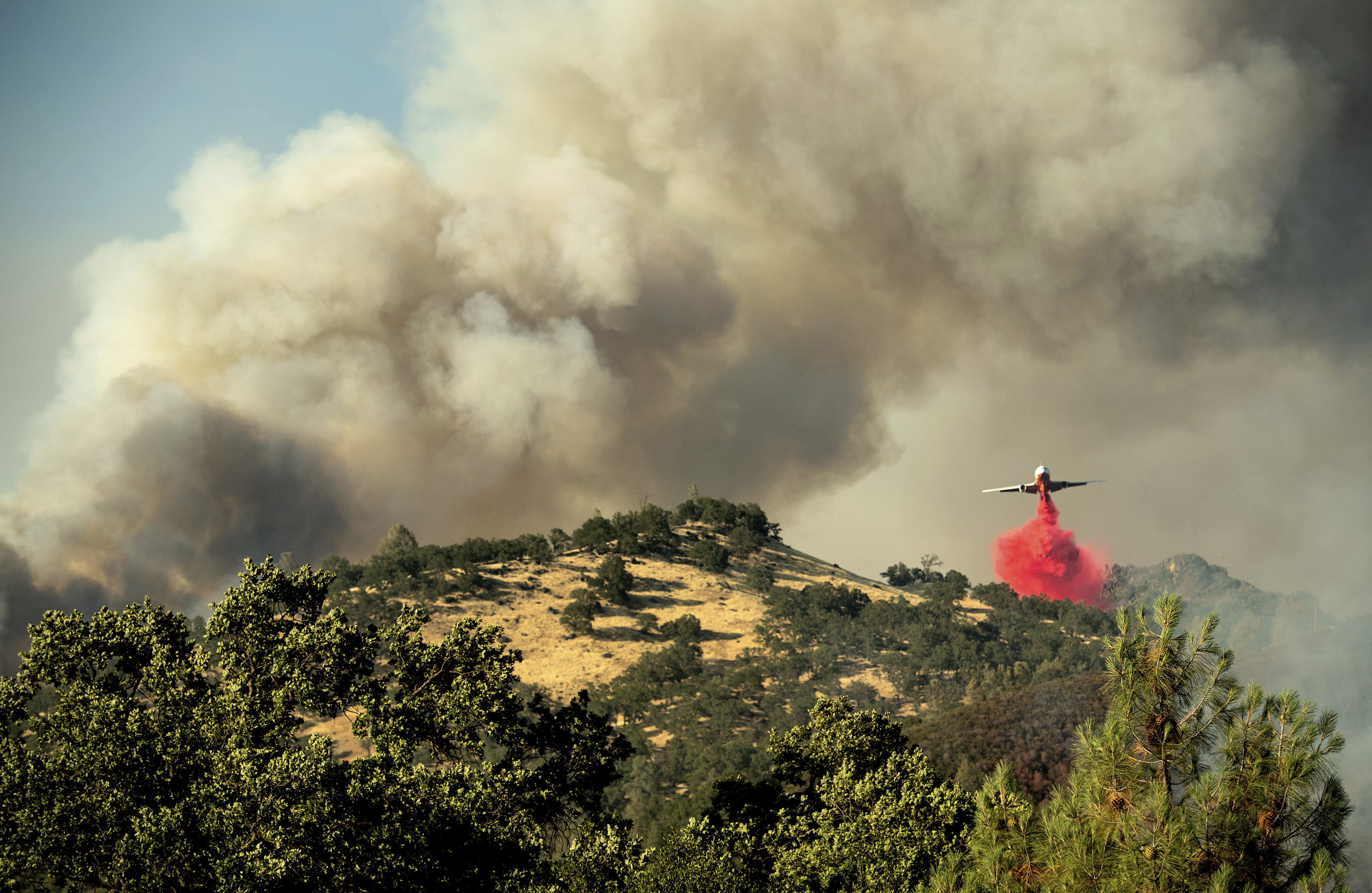 <p>An air tanker drops retardant on a wildfire above the Spring Lakes community on Sunday, June 24, 2018., near Clearlake Oaks, Calif. Wind-driven wildfires destroyed buildings and threatened hundreds of others Sunday as they raced across dry brush in rural Northern California. (Photo: Noah Berger/AP) </p>