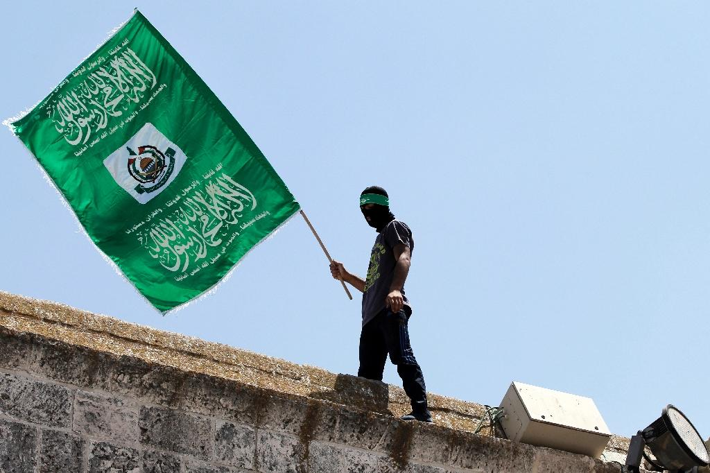 A Palestinian man waves the green flag of the Islamist movement Hamas during a demonstration in Jerusalem on July 3, 2015