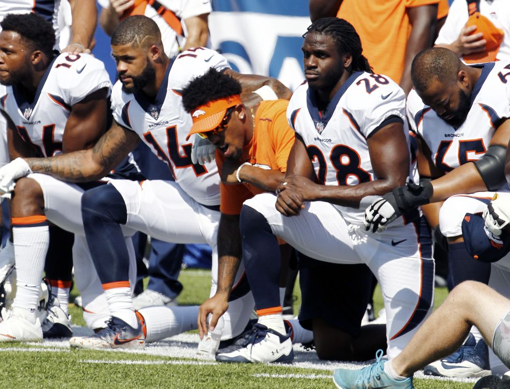Broncos players, including Jamaal Charles (28) kneel during the national anthem prior to a Week 3 game. (AP)