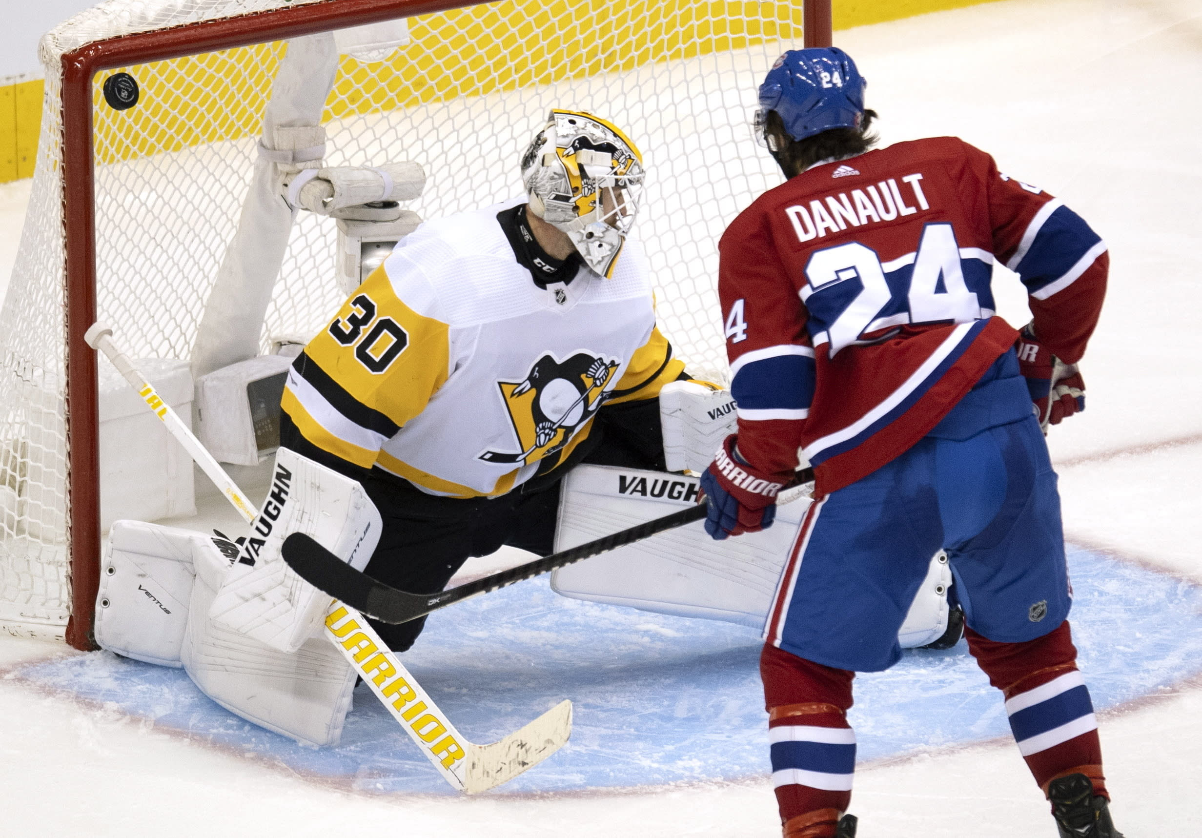 Montreal Canadiens centre Phillip Danault (24) watches as the puck bounces off the post behind Pittsburgh Penguins goaltender Matt Murray (30) during the third period of an NHL hockey playoff game Wednesday, Aug. 5, 2020 in Toronto. (Frank Gunn/The Canadian Press via AP)