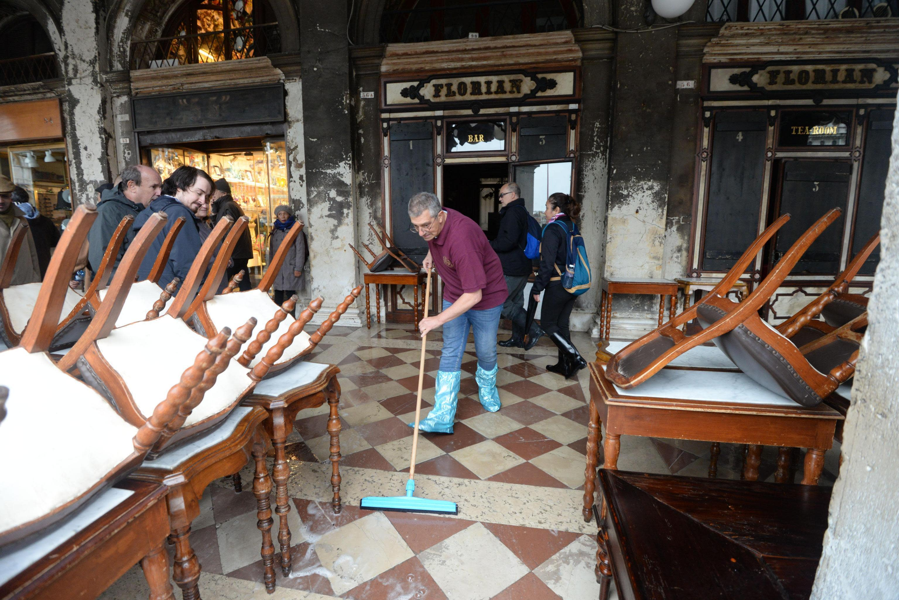 A man cleans water out of the historical Florian cafe, in Venice, Italy, Wednesday, Nov. 13, 2019. The high-water mark hit 187 centimeters (74 inches) late Tuesday, Nov. 12, 2019, meaning more than 85% of the city was flooded. The highest level ever recorded was 194 centimeters (76 inches) during infamous flooding in 1966. (Andrea Merola/ANSA via AP)