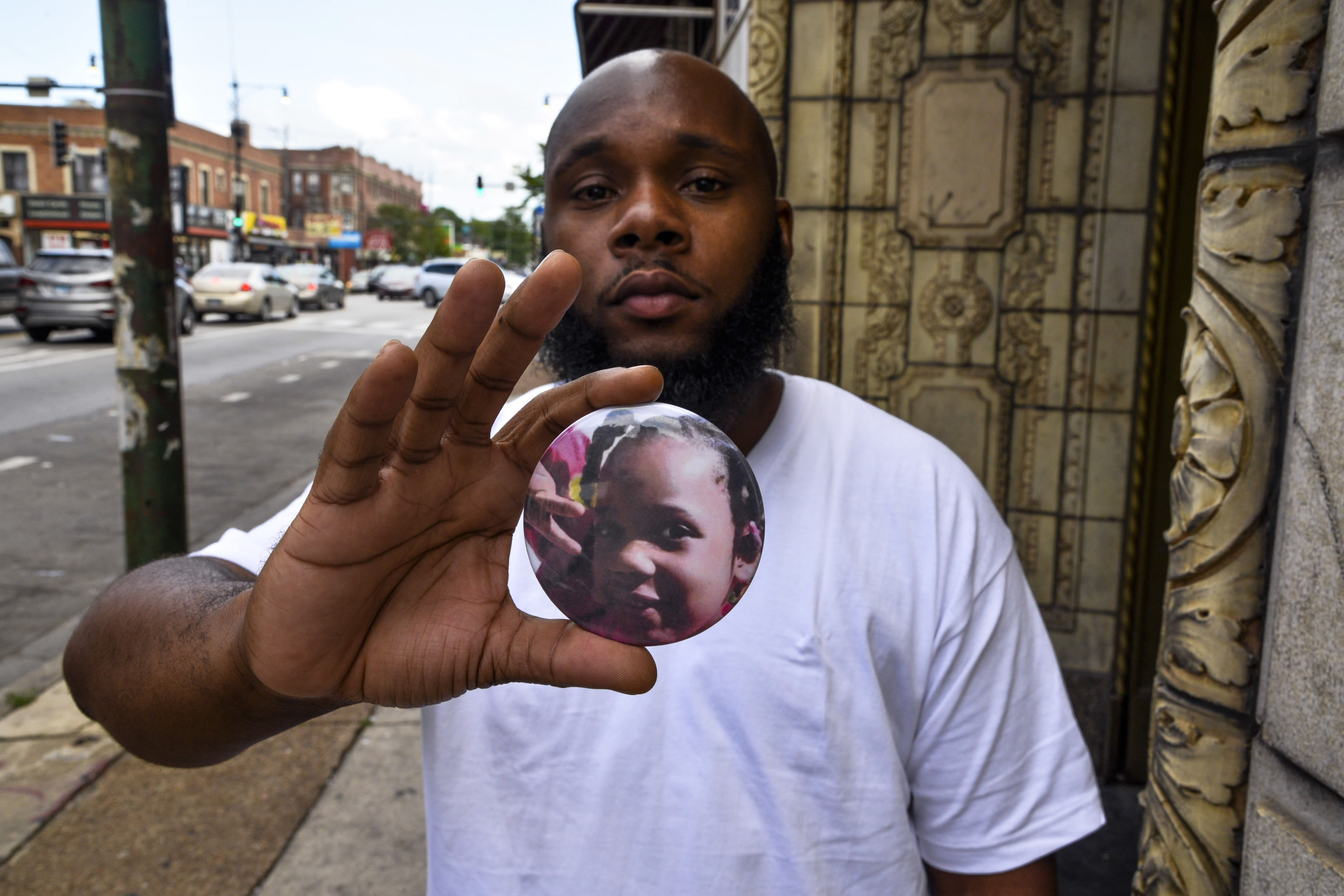 Nathan Wallace stands outside of his home holding a button showing his daughter, Natalia Wallace, on Monday, Aug. 3, 2020, in Chicago. Natalia, 7, was killed on the west side of Chicago on July 4, 2020. (AP Photo/Matt Marton)