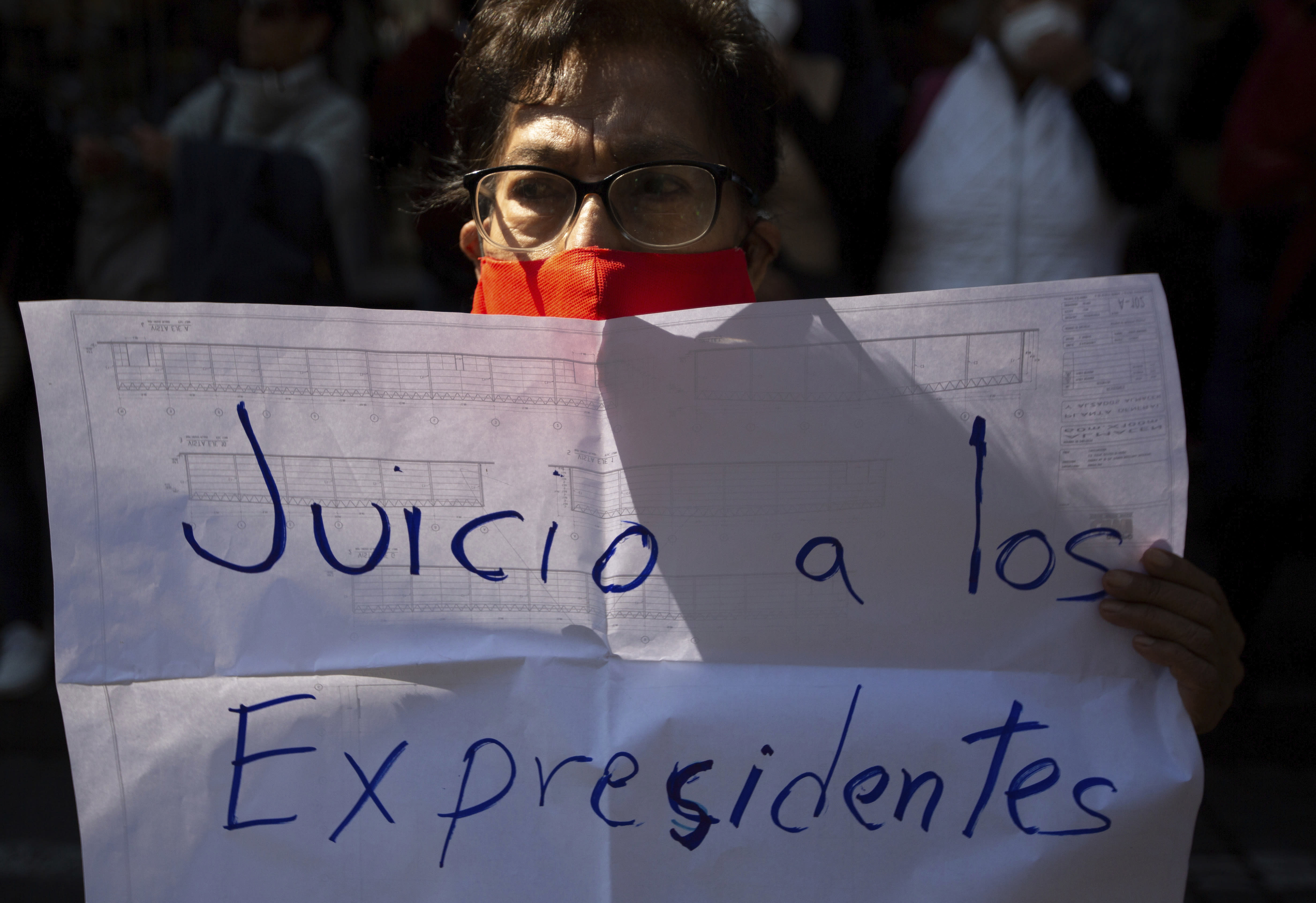 """A supporter of Mexico's President Andres Manuel Lopez Obrador holds the Spanish message: """"Trial of former presidents"""" during a demonstration outside the Supreme Court in Mexico City, Thursday, Oct. 1, 2020. The court is scheduled to decide whether the president's proposal to hold a popular vote to decide whether or not to pursue former presidents on corruption charges stands up to scrutiny. (AP Photo/Fernando Llano)"""