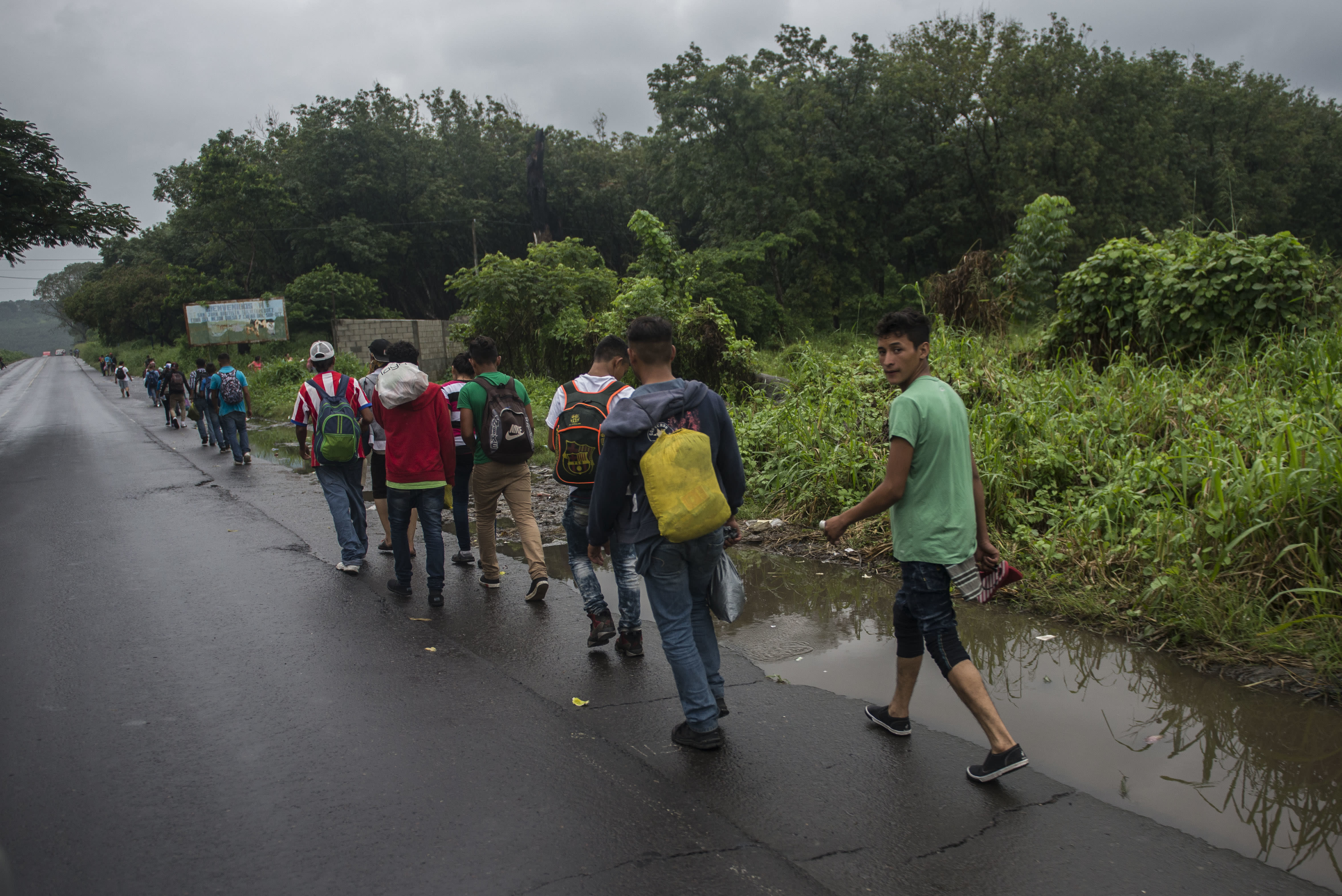 Honduran migrants are seen walking along a highway in Cocales, Gautemala, on their way to the U.S. border, Thursday, Oct. 18, 2018. Many of the more than 2,000 Hondurans in a migrant caravan trying to wend its way to the United States left spontaneously with little more than the clothes on their backs and what they could quickly throw into backpacks. (AP Photo/Oliver de Ros)'