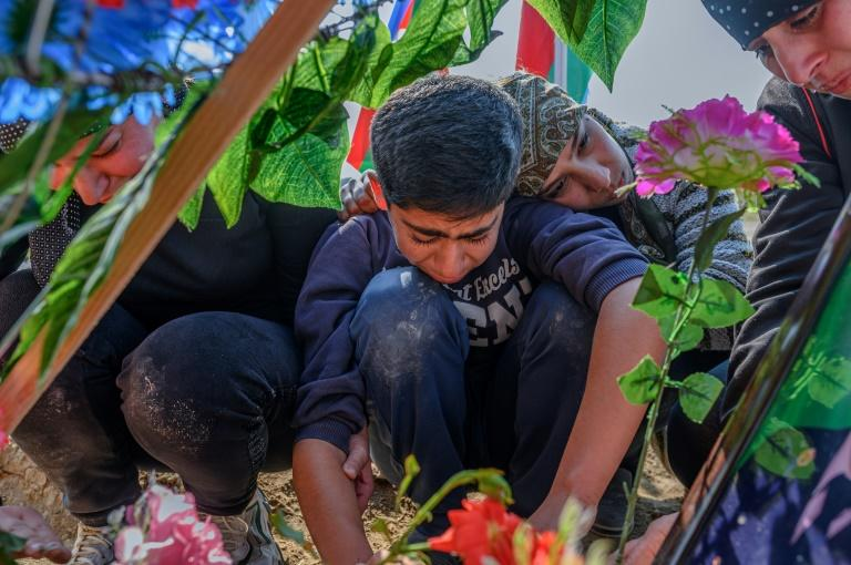 Family members of an Azerbaijani soldier grieve at his grave