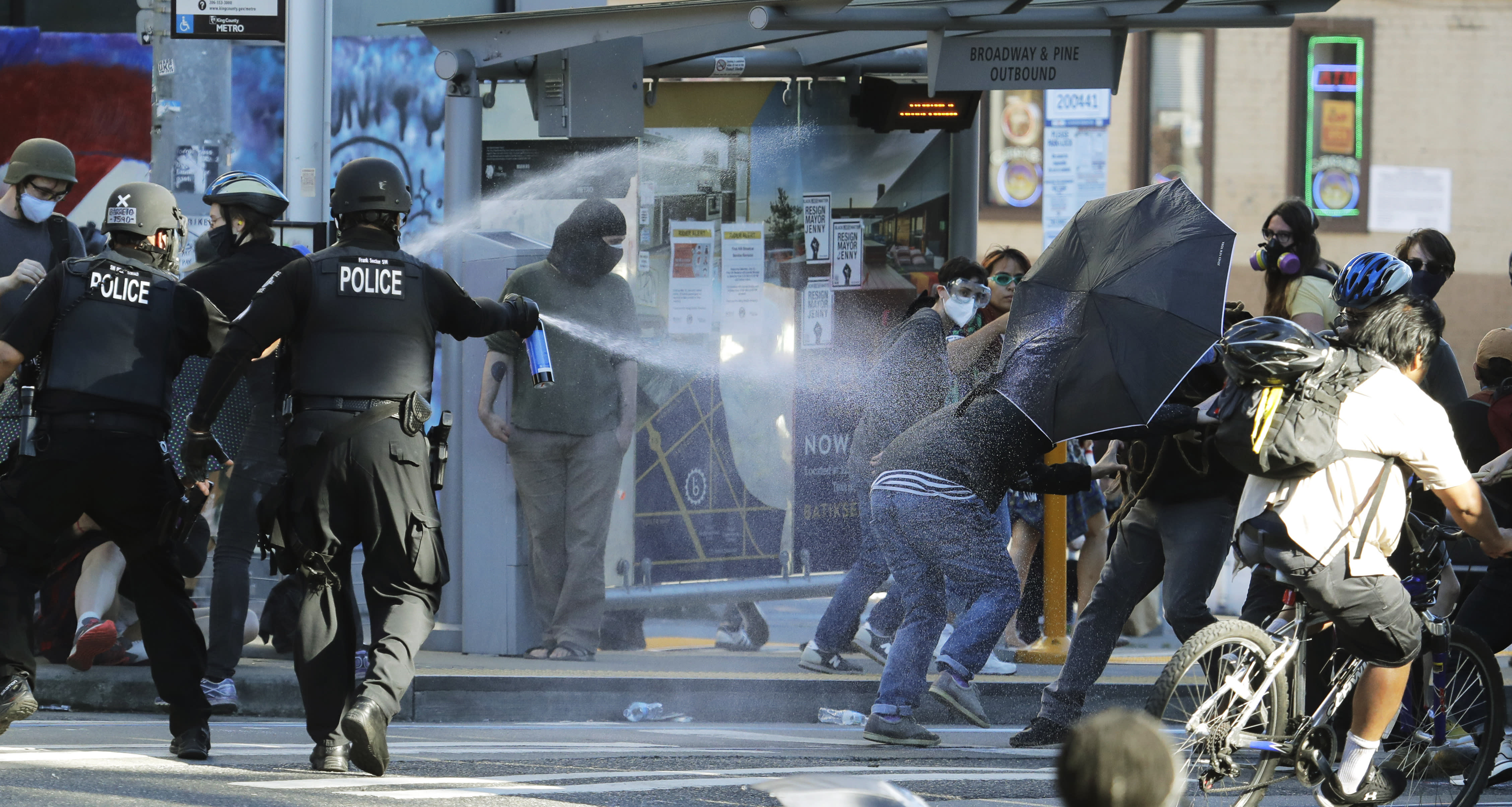 Police pepper spray protesters Saturday, July 25, 2020, near Seattle Central Community College in Seattle. A large group of protesters were marching Saturday in Seattle in support of Black Lives Matter and against police brutality and racial injustice. (AP Photo/Ted S. Warren)