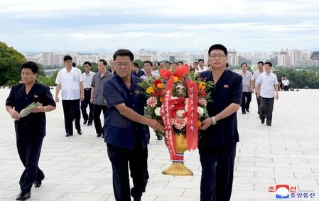 People hold floral tributes in North Korea
