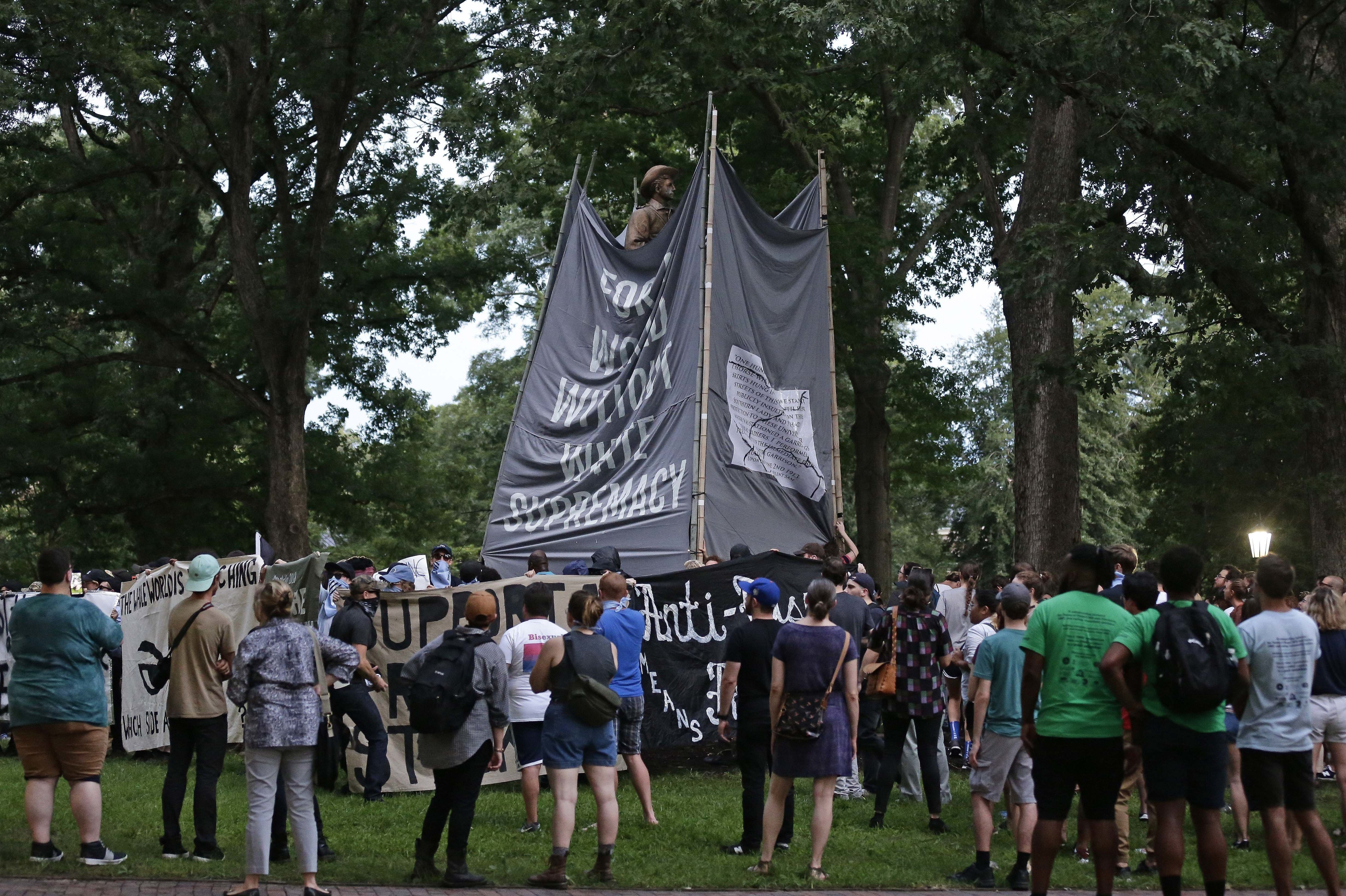 FILE - In this Monday, Aug. 20, 2018 file photo, banners are used to cover the statue known as Silent Sam as people gather during a rally to remove the confederate statue from campus at the University of North Carolina in Chapel Hill, N.C. Police are filing charges against three people who they say helped bring down the Confederate statue at North Carolina's flagship university. University of North Carolina Police issued a statement Friday, Aug. 24, 2018, that the department has filed warrants for three people on charges of misdemeanor rioting and defacing a public monument. (AP Photo/Gerry Broome, File)