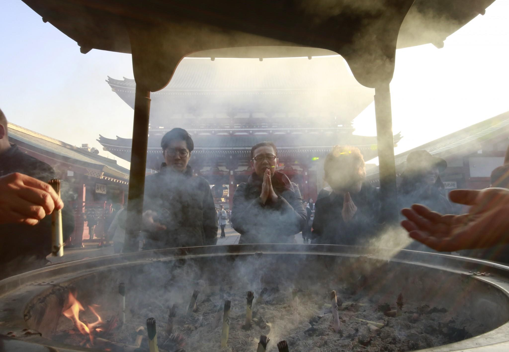<p>Worshippers gather around a huge incense burner as they offer their prayers at the Sensoji Buddhist temple in Asakusa district of Tokyo, Tuesday, Dec. 20, 2016. Asakusa annually draws many tourists from around the world. (Photo: Shizuo Kambayashi/AP) </p>