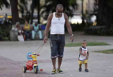 A man walks with his son in Havana