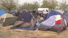 Wildfire evacuees living in tents near parking lot