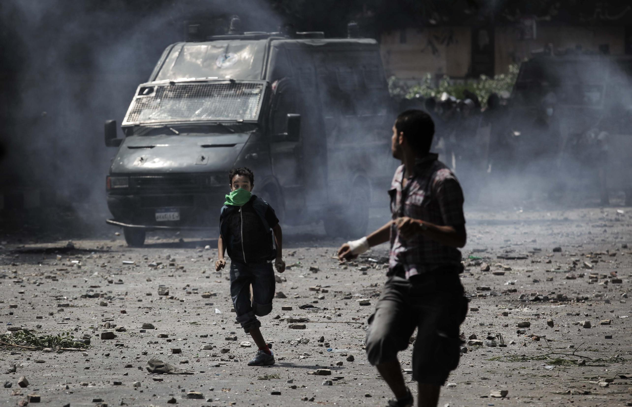 Egyptian protesters run during clashes with riot police, background, outside the U.S. embassy in Cairo, Egypt, Thursday, Sept. 13, 2012. Tens were injured in clashes in front of the U.S. embassy in Cairo, the state TV reported on Thursday, quoting Egypt's Health Ministry. (AP Photo/Nasser Nasser)