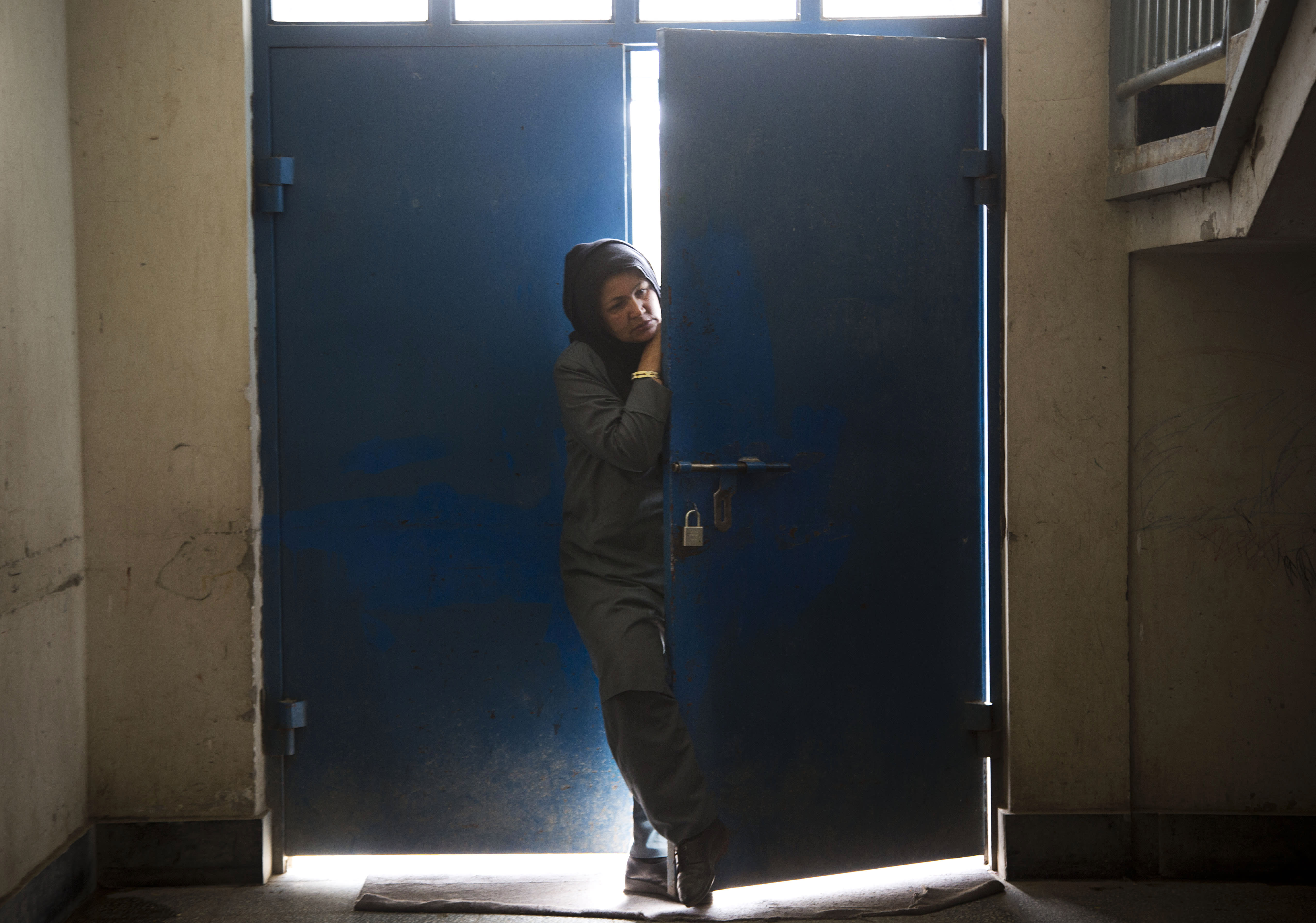 "Picture taken March 28, 2013 shows an Afghan female guard peering through the main gate at Badam Bagh, Afghanistan's central women's prison, in Kabul, Afghanistan. 202 women living in the six- year- old jail, the majority of the women are serving sentences of up to seven years for leaving their husbands, refusing to accept a marriage arranged by their parents, or choosing to leave their parent's home with a man of their choice, all so-called ""moral"" crimes(. AP Photo/Anja Niedringhaus)"